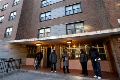 Men gather outside of the building where a man was allegedly shot by a police officer the night before at the Louis Pink Houses public housing complex, Friday, Nov. 21, 2014, in Brooklyn borough of New York.  A rookie police officer with his gun drawn shot to death 28-year-old Akai Gurley, an unarmed, innocent man in the darkened stairwell of the crime-ridden public housing complex, New York City police officials said Friday.  The shooting appeared to be an accident, Police Commissioner William Bratton said at a news conference.  (AP Photo/Julio Cortez)