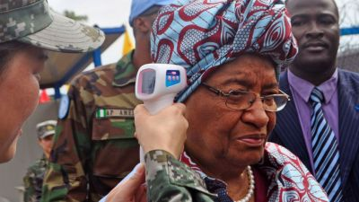 """Liberian President Ellen Johnson Sirleaf, center, temperature is taken by a Chinese soldier, left, before the opening of a new Ebola virus clinic sponsored by China, in Monrovia, Liberia, Tuesday, Nov. 25, 2014, Liberia got another 100 treatment beds in the fight against Ebola on Tuesday, as yet another Sierra Leonean doctor became infected with the disease sweeping West Africa. Liberian President Ellen Johnson Sirleaf toured the Ebola treatment center built by China, calling it """"first-class."""" (AP Photo/ Abbas Dulleh)"""