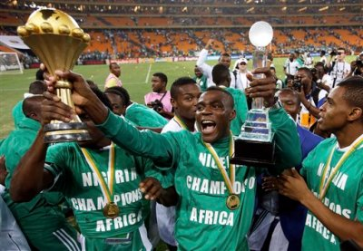 """This is a Sunday, Feb. 10, 2013 file photo of Nigeria's Emmanuel Emenike as he holds the trophy after they defeated Burkina Faso in the final to win the African Cup of Nations at the Soccer City Stadium in Johannesburg, South Africa. Morocco has been disqualified from the 2015 African Cup of Nations after refusing to host the tournament because of Ebola, and a new host country will be chosen. The Confederation of African Football said Tuesday Nov. 11, 2014 it has received """"some applications"""" from possible replacement hosts. CAF didn't announce who the candidates were. (AP Photo/Armando Franca, File)"""