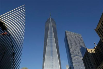 One World Trade Center, center, stands between the transportation hub, left, still under construction, and 7 World Trade Center, second from right, Monday, Nov. 3, 2014 in New York. Thirteen years after the 9/11 terrorist attack, the resurrected World Trade Center is again opening for business, marking an emotional milestone for both New Yorkers and the United States as a whole. Publishing giant Conde Nast will start moving Monday into One World Trade Center, a 104-story, $3.9 billion skyscraper that dominates the Manhattan skyline. (AP Photo/Mark Lennihan)