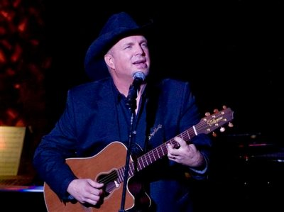 "In this Nov. 17, 2014 file photo, Garth Brooks performs the 2014 ASCAP Centennial Awards, benefiting the ASCAP Foundation and its music education, talent development and humanitarian activities, at the Waldorf-Astoria in New York. Brooks has canceled a Thanksgiving appearance on NBC's ""Tonight"" show because he said it ""seemed distasteful"" given the reaction to the decision not to prosecute Ferguson police officer Darren Wilson for the shooting of Michael Brown this summer. NBC on Wednesday, Nov. 26, confirmed the postponement, saying Brooks was being replaced on the show by Whoopi Goldberg and Tom Colicchio. (Photo by Stephen Chernin/Invision/AP, File)"