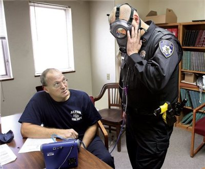 Alton, Ill., Fire Department engineer Bob Eichen, left, uses a machine to run a series of five tests on the gas mask of Alton Police officer Michael Beaber, right, at the Don Twichell Memorial Fire Station in Alton, Monday Nov. 10, 2014.  The Alton, Ill., Police Department has been preparing for any possible civil unrest or the need to assist other departments for over a month in advance of the verdict by the Grand Jury in the Ferguson, Mo., police shooting death of Michael Brown. (AP Photo/The Telegraph, John Badman)