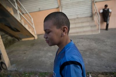 In this Tuesday, Nov. 25, 2014 photo, Roberto Castellanos, walks to work, in Tegucigalpa, Honduras. Wise beyond his years, Roberto says he knows that many people consider child labor to be exploitation, but he sees it as opportunity _ a means to survive the gang-controlled capital of a country with the world's highest homicide rate. (AP Photo/Esteban Felix)