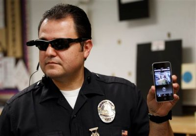 In this Jan. 15, 2014 file photo, Los Angeles Police Sgt. Daniel Gomez demonstrates a video feed from his camera into his cellphone during a on-body camera demonstration for the media, in Los Angeles. Officers in one of every six departments around the country are now patrolling with these tiny cameras on their chests, lapels or sunglasses, and that number is growing. Most civil libertarians support their expansion despite concerns about the development of policies governing their use and their impact on privacy. (AP Photo/Damian Dovarganes,File)