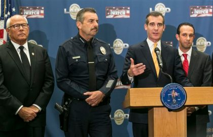 Los Angeles Mayor Eric Garcetti, third from left, announces a plan to equip 7,000 Los Angeles police officers with on-body cameras by next summer during a news conference in Los Angeles on Tuesday, Dec. 16, 2014. From left, Los Angeles police commission President Steve Soboroff, Police Chief Charlie Beck, Garcetti, and Los Angeles Councilman Mitchell Englander. (AP Photo/Damian Dovarganes)
