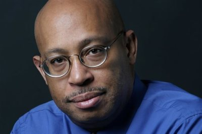 This April 15, 2004 photo shows Michel du Cille, a photographer and former photo editor with The Washington Post. Three time Pulitzer Prize winner, du Cille died Thursday Dec. 11, 2014 while on assignment  chronicling Ebola patients and their caretakers for the Post in Liberia. He was 58. (AP Photo/The Washington Post, Julia Ewan)