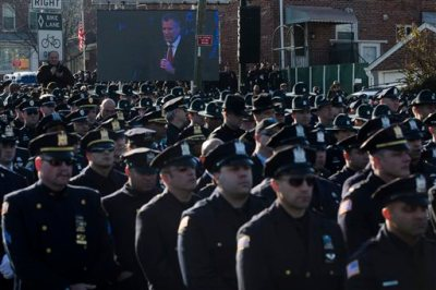 This Dec. 27, 2014, file photo shows police officers turning their backs as New York City Mayor Bill de Blasio speaks at the funeral of New York city police officer Rafael Ramos in the Glendale section of Queens, in New York. Mayor Bill de Blasio is winding down his first year in office, which saw success at fulfilling many of his liberal campaign promises. But the year ends with his young mayoralty facing its biggest crisis yet: an open rebellion from police officers who don't believe the mayor supports them. (AP Photo/John Minchillo)