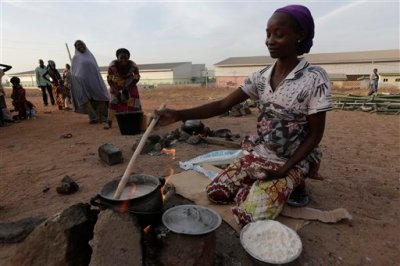 An unidentified woman who fled her home following an attack by Islamist militants, in Mubi, prepares a meal at the camp for internally displaced people in Yola, Nigeria, Friday Nov. 28, 2014. Some thousands of people have fled their homes in recent times due to Boko Haram attacks. (AP Photo/Sunday Alamba)