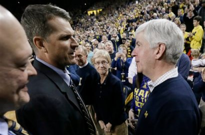 Michigan football coach Jim Harbaugh meets with Michigan Gov. Rick Snyder, right, during halftime of an NCAA college basketball game between Michigan and Illinois in Ann Arbor, Mich., Tuesday, Dec. 30, 2014. (AP Photo/Carlos Osorio)