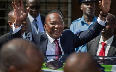 In this Saturday, March 2, 2013 file photo, Kenya's then President-Elect Uhuru Kenyatta waves to supporters after leaving the National Election Center where final election results were announced declaring he would be the country's next president, in Nairobi, Kenya Saturday, March 9, 2013. The International Criminal Court's chief prosecutor dropped all crimes against humanity charges against Kenya's president Uhuru Kenyatta on Friday, Dec. 5, 2014 highlighting the court's problems in bringing to justice the high-ranking officials it has accused of atrocities. (AP Photo/Ben Curtis, File)