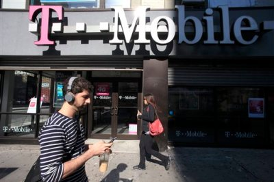 In this Sept. 12, 2012 file photo, a man uses a cellphone as he passes a T-Mobile store in New York. T-Mobile on Tuesday, Dec. 16, 2014 announced it is now letting customers carry over their unused cellular-data allotments for up to a year. (AP Photo/Mark Lennihan, File)