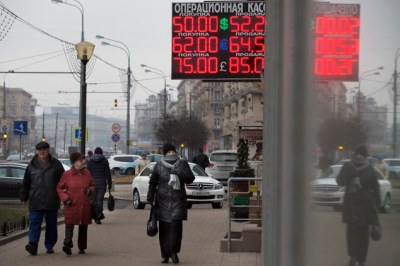 People walk past a display with currency exchange rates in central Moscow, Russia, Monday, Dec. 1, 2014. (AP Photo/Alexander Zemlianichenko)