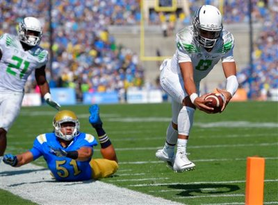 In this Oct. 11, 2014, file photo, Oregon quarterback Marcus Mariota, right, dives in for a touchdown as UCLA linebacker Aaron Wallace, center, misses the tackle and running back Royce Freeman looks on during the first half of an NCAA college football game in Pasadena, Calif. Oregon quarterback Mariota, Alabama receiver Amari Cooper and record-breaking Wisconsin running back Melvin Gordon are the finalists for the Heisman Trophy announced Monday, Dec. 8. (AP Photo/Mark J. Terrill, File)