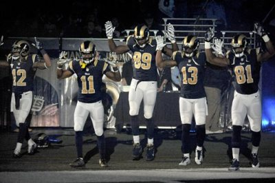"Members of the St. Louis Rams raise their arms in awareness of the events in Ferguson, Mo.,  as they walk onto the field during introductions before an NFL football game against the Oakland Raiders, Sunday, Nov. 30, 2014, in St. Louis.  The players said after the game, they raised their arms in a ""hands up"" gesture to acknowledge the events in Ferguson. (AP Photo/L.G. Patterson)"