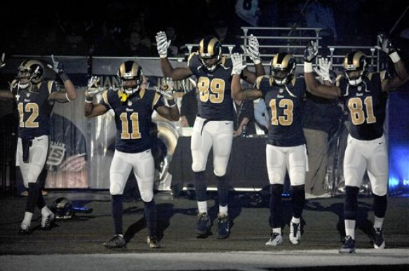 """Members of the St. Louis Rams raise their arms in awareness of the events in Ferguson, Mo.,  as they walk onto the field during introductions before an NFL football game against the Oakland Raiders, Sunday, Nov. 30, 2014, in St. Louis.  The players said after the game, they raised their arms in a """"hands up"""" gesture to acknowledge the events in Ferguson. (AP Photo/L.G. Patterson)"""