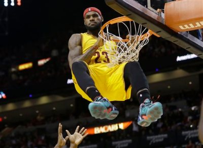Cleveland Cavaliers forward LeBron James (23) hangs onto the basket after a dunk during the second half of an NBA basketball game against the Miami Heat, Thursday, Dec. 25, 2014, in Miami. James was called for a technical foul on the play. The Heat won 101-91. (AP Photo/Lynne Sladky)
