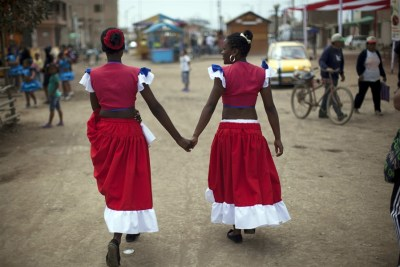 Norma Vargas Portillo, right, and Milagros Gallardo walk hand in hand before performing a traditional Afro-Peruvian dance during festivities in honor of Santa Efigenia in La Quebrada, Peru, Sept. 23, 2012. (Rodrigo Abd/AP)