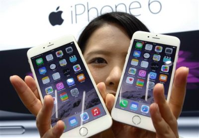 In this Sept. 19, 2014 file photo, a customer shows off the new Apple iPhone 6 and 6 Plus at a store in Tokyo. Apple Inc. on Thursday, Jan. 8, 2015 said that its App Store customers set a record for billings by spending nearly half a billion dollars on apps and in-app purchases during January's first week. It said New Year's Day was also the single biggest day ever in App Store sales history. (AP Photo/Shizuo Kambayashi, File)