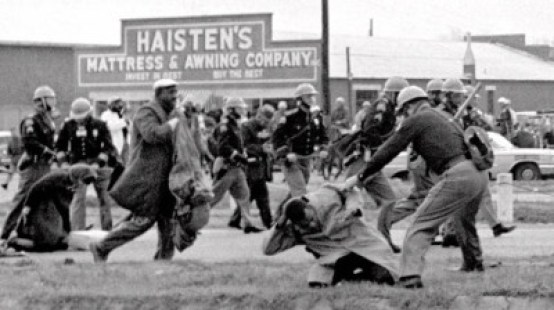 """Alabama state troopers swing nightsticks to break up the """"Bloody Sunday"""" voting march in Selma, Ala., on March 7, 1965. John Lewis, front right, of the Student Non-violent Coordinating Committee, is put on the ground by a trooper. (Associated Press)"""