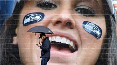 A pedestrian walks past a large photo of a cheering Seattle Seahawks' fan outside the team's stadium Tuesday, Feb. 3, 2015, in Seattle. The grief, anger and bewilderment felt by many Seahawks fans after the team's loss to the New England Patriots in the Super Bowl shows little sign of abating, even days later. (AP Photo/Elaine Thompson)