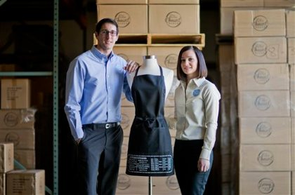 """In this Sunday, Feb. 22, 2015 photo, Daniel Rensing, left and his wife Stephanie, owners of The Smart Baker, pose with their first product, an apron with upside down measurement conversions, at their warehouse in Rockledge, Fla. Annual revenue for their company is close to $1 million, up from $130,000 before their March 2012 appearance on the reality TV show """"Shark Tank"""". (AP Photo/David Goldman)"""