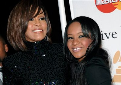 In this Feb. 12, 2011, file photo, singer Whitney Houston, left, and daughter Bobbi Kristina Brown arrive at an event in Beverly Hills, Calif. Messages of support were being offered Monday, Feb. 2, 2015, as people awaited word on Brown, who authorities say was found face down and unresponsive in a bathtub over the weekend in a suburban Atlanta home. (AP Photo/Dan Steinberg, File)