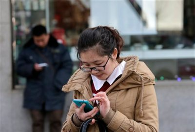 Chinese people check on their smartphones on a street in Beijing Monday, Feb. 16, 2015. On the Internet, in college classrooms and in corporate offices, the Chinese Communist Party has raised the virtual wall separating the world's most populous country from the rest of the globe. Experts say it reflects a distrust of outside influences that party thinks could threaten its control on society. (AP Photo/Andy Wong)
