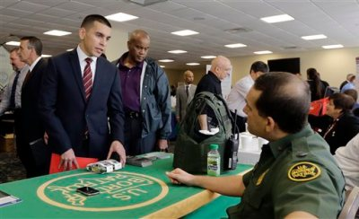 In this photo taken Friday, Feb. 6, 2015, U.S. Marine Corps Veteran Christopher Triana,left, talks about job probabilities to U.S. Border Patrol agent Frank Miller, right, at the annual Veterans Career and Resource Fair in Miami. The U.S. Labor Department reports on the number of people who applied for unemployment benefits for the week ending Feb. 21 on Thursday, Feb. 26, 2015. (AP Photo/Alan Diaz)
