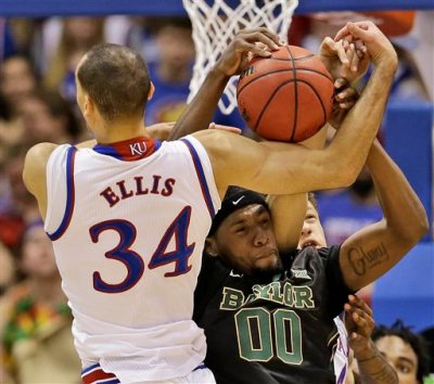 Kansas's Perry Ellis (34) and Royce O'Neale (00) battle for a rebound during the first half of an NCAA college basketball game Saturday, Feb. 14, 2015, in Lawrence, Kan. (AP Photo/Charlie Riedel)