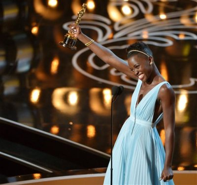 """In this March 2, 2014 file photo, Lupita Nyong'o accepts the award for best actress in a supporting role for """"12 Years a Slave"""" during the Oscars in Los Angeles. Nyong'o dazzled Hollywood and the Oscar-viewing public through awards season last year. The Mexican-born, Kenyan-raised actress was a central part last year to an Academy Awards flush with faces uncommon to the Oscar podium. There was Ellen DeGeneres, a proud lesbian, hosting. There was the first Latino, Alfonso Cuaron, winning best director. There was the black filmmaker Steve McQueen hopping for joy after his """"12 Years a Slave"""" won best picture. (Photo by John Shearer/Invision/AP, File)"""