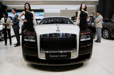 In this Nov. 21, 2013 file photo, models pose beside the Rolls-Royce Canton Glory at the company's booth during Guangzhou 2013 Auto Show in China's southern city of Guangzhou. (AP Photo/Kin Cheung, File)