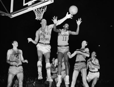 In this April 1955 file photo, Fort Wayne's Mel Hutchins (9) and Syracuse's Earl Lloyd (11) reach for the ball during an NBA basketball game in Indianapolis. Lloyd, the first black player in NBA history, died Thursday, Feb. 26, 2015. He was 86. Lloyd's alma mater, West Virginia State, confirmed the death. It did not provide details. Lloyd made his NBA debut in 1950 for the Washington Capitals, just before fellow black players Sweetwater Clifton and Chuck Cooper played their first games. (AP Photo/File)