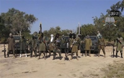 In his file image taken from video released late Friday evening, Oct. 31, 2014, by Boko Haram, Abubakar Shekau, centre, the leader of Nigeria's Islamic extremist group.  Boko Haram fighters have shot or burned to death about 90 civilians and wounded 500 in ongoing fighting in a Cameroonian border town near Nigeria, officials in Cameroon said Thursday, Feb. 5, 2015. (AP Photo/Boko Haram,File)