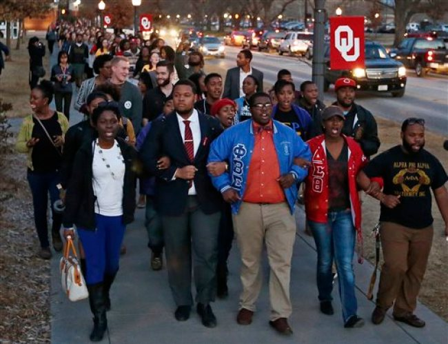 In this March 10, 2015, photo, University of Oklahoma students march to the now closed University of Oklahoma's Sigma Alpha Epsilon fraternity house  during a rally in reaction to an incident in which members of a fraternity were caught on video chanting a racial slur, in Norman, Okla. Many colleges are clamping down on campus fraternities after their reputations are sullied by race-tainted incidents. Even with a school's sometimes swift and hard action, episodes such as the racist chants by members of the Sigma Alpha Epsilon chapter at the University of Oklahoma still surface.  (AP Photo/Sue Ogrocki)