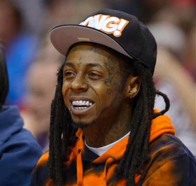 In this Wednesday, Feb. 28, 2014 file photo, singer Lil Wayne watches the Los Angeles Clippers play the Houston Rockets during the first half of an NBA basketball game, in Los Angeles. Police have responded to a report of 4 people shot at the Miami Beach home of rapper Lil Wayne. Miami Beach Det. Vivian Thayer says police units responded Wednesday, March 11, 2015, after someone called to say four people had been shot at the waterfront home. (AP Photo/Mark J. Terrill, File)