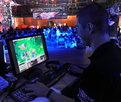 In this Aug. 7, 2009, file photo, a participant plays a computer game during the Intel Friday Night Game, a competition of the ESL, Electronic Sports League, in Dresden, Germany. The Electronic Sports League and live event broadcaster BY Experience announced plans Tuesday, March 17, 2015, to bring a series of live esports events to 1,500 to 2,000 movie theaters around the world. (AP Photo/Matthias Rietschel, File)