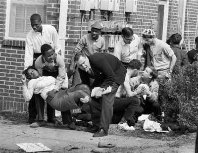 "In this March 7, 1965 file photo, S.W. Boynton is carried and another injured man tended to after they were injured when state police broke up a demonstration march in Selma, Ala. Boynton, wife of a real estate and insurance man, has been a leader in civil rights efforts. The day, which became known as ""Bloody Sunday,"" is widely credited for galvanizing the nation's leaders and ultimately yielded passage of the Voting Rights Act of 1965. (AP Photo/File)"