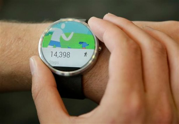 FILE - In this June 25, 2014 file photo ,a man wears a Moto 360 by Motorola, an Android Wear smartwatch, on the demo floor at Google I/O 2014 in San Francisco. (AP Photo/Jeff Chiu, File)