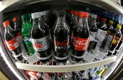 This Oct. 1, 2014 file photo taken with a fisheye lens shows a shelf of diet and regular soft drinks in a refrigerator at K & D Market in San Francisco. U.S. soda volume declined for the tenth straight year in 2014, with diet sodas faring worse than their regular counterparts, according to a report released Thursday, March 26, 2015. (AP Photo/Jeff Chiu, File)