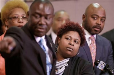 Samaria Rice, center, the mother of Tamir Rice, a 12-year-old boy fatally shot by a Cleveland police officer, watches the video of Tamir's shooting during a news-conference Tuesday, March 3, 2015, in Cleveland. Attorney Benjamin Crump, left, and attorneys Walter Madison, right, watch.  Rice and her attorneys talked about the city's response to the lawsuit, a day after Cleveland Mayor Frank Jackson apologized for wording in a court document in which the city said the boy died as a result of his own actions. (AP Photo/Tony Dejak)