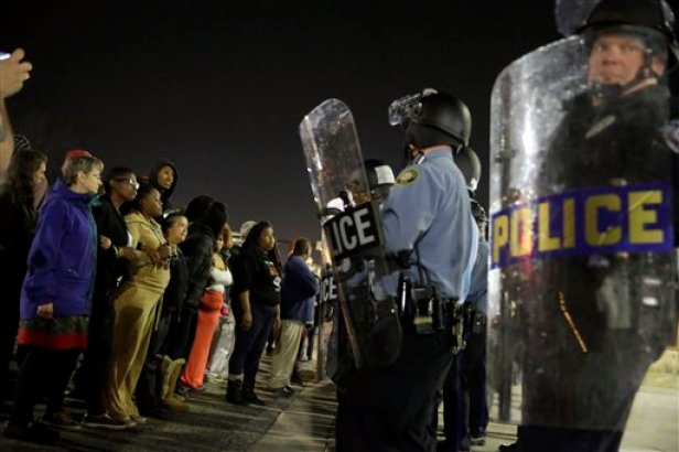 Police and protesters square off outside the Ferguson Police Department, Wednesday, March 11, 2015, in Ferguson, Mo. Earlier in the day, the resignation of Ferguson police chief Thomas Jackson was announced in the wake of a scathing Justice Department report prompted by the fatal shooting of an unarmed black 18-year-old by a white police officer. (AP Photo/Jeff Roberson)