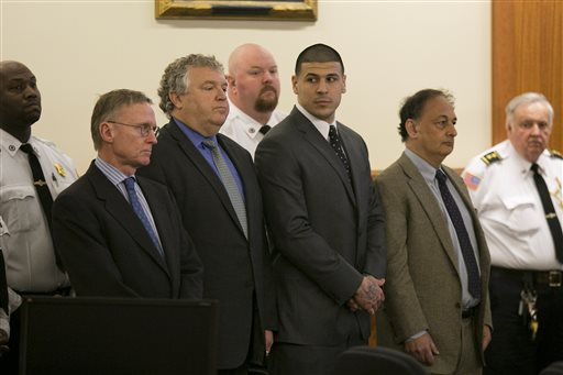 Former NFL player Aaron Hernandez stands with his defense attorneys as he hears his verdict in his murder trial at the Bristol County Superior Court in Fall River