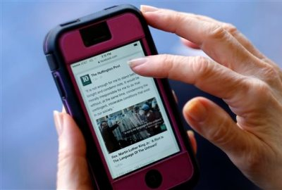 "In this Tuesday, April 28, 2015 photo, an unidentified person uses a mobile phone to read the news from The Huffington Post on Facebook, in Los Angeles. ""State of the News Media 2015,"" published Wednesday, April 29, 2015, by the Pew Research Center's Journalism Project found that nearly half of Web users learn about politics and government from Facebook, roughly the same percentage as those who seek the news through local television and double those who visit Yahoo or Google News. (AP Photo/Richard Vogel)"