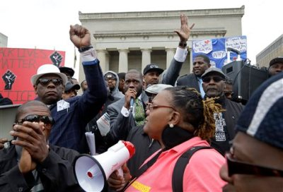 The Rev. Jamal Bryant, center, addresses protestors before a march for Freddie Gray, Thursday, April 23, 2015, in Baltimore. Gray died from spinal trauma a week after being arrested by a group of officers, hoisted into police van and driven to a Baltimore station. (AP Photo/Patrick Semansky)