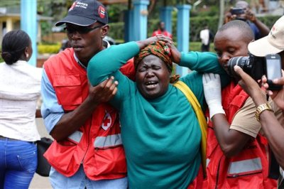 Kenya Red Cross staff assist a woman after she viewed the body of a relative killed in Thursday's attack on a university, at Chiromo funeral home, Nairobi, Kenya, Friday, April 3, 2015. Al-Shabab gunmen rampaged through a university in northeastern Kenya at dawn Thursday, killing scores of people in the group's deadliest attack in the East African country. Four militants were slain by security forces to end the siege just after dusk. (AP Photo)