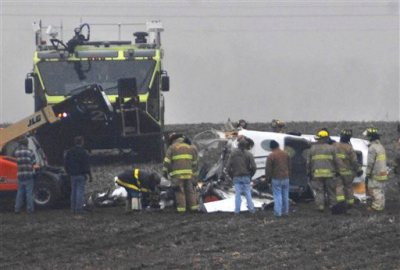 Investigators work in a thick fog at the site of small plane crash near Bloomington, Ill., Tuesday, April 7, 2015, that has claimed the lives of seven people. The Cessna 414 took off from Indianapolis and crashed just short of the Central Illinois Regional Airport in Bloomington after midnight. The plane was returning from the NCAA Final Four college basketball tournament in Indianapolis. (AP Photo/The Pantagraph, David Proeber)