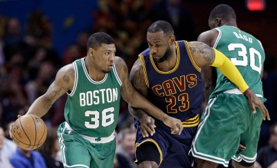 Boston Celtics' Marcus Smart (36) drives past Cleveland Cavaliers' LeBron James (23) as Celtics' Brandon Bass (30) blocks during the first quarter of an NBA basketball game Friday, April 10, 2015, in Cleveland. (AP Photo/Tony Dejak)
