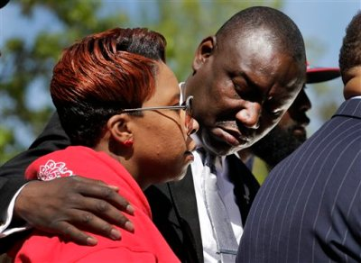 Family attorney Benjamin L. Crump, right, puts his arm around Lesley McSpadden, the mother of Michael Brown, during a news conference Thursday, April 23, 2015, in Clayton, Mo. The parents of Michael Brown filed a wrongful-death lawsuit Thursday against the city of Ferguson, Mo., over the fatal shooting of their son by a white police officer, a confrontation that sparked a protest movement across the United States. (AP Photo/Jeff Roberson)