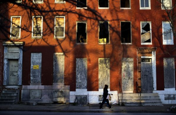 A woman walks past blighted row houses in Baltimore. (AP Photo/Patrick Semansky)