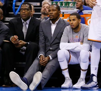In this March 4, 2015, file photo, injured Oklahoma City Thunder forward Kevin Durant, center, watches from the bench with guard D.J. Augustin, right, and assistant coach Mark Bryant, left, during the first quarter of an NBA basketball game against the Philadelphia 76ers in Oklahoma City. Durant will have bone graft surgery next week to deal with a fractured bone in his right foot, and he will miss the rest of the season, the Oklahoma City Thunder announced Friday, March 27, 2015. (AP Photo/Sue Ogrocki, File)